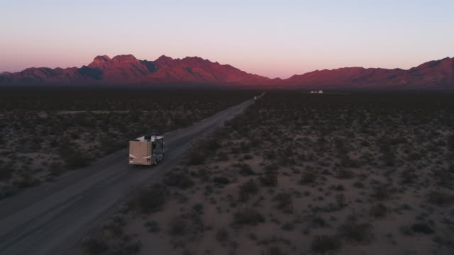 A camper driving over a sandy road during sunset in the desert
