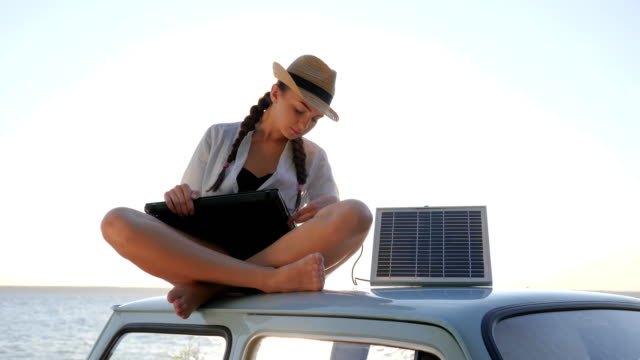 camper girl in backlight sits on car roof with solar array charges laptop and waving hello, female sitting on vintage car video