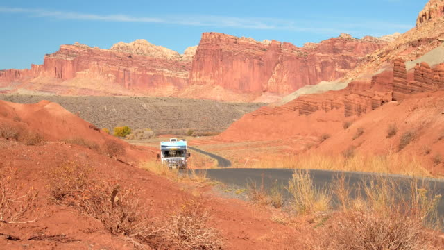 RV Camper traveling past mesa and butte mountain formations in red rock desert