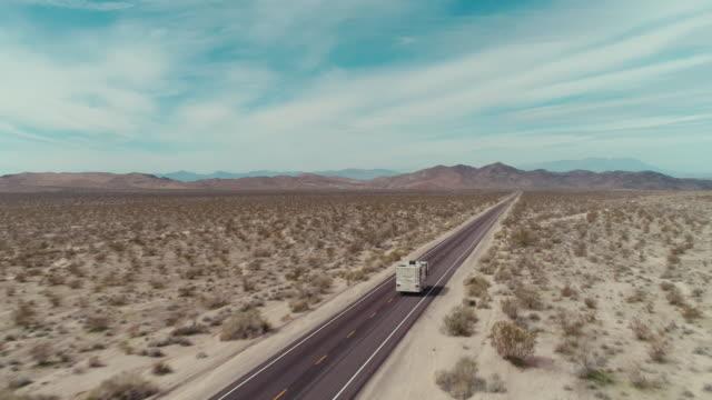 stockvideo's en b-roll-footage met een camper die over een weg in het midden van de mojavewoestijn drijft - caravan