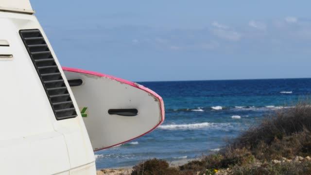 Camper van with surf board on beach video