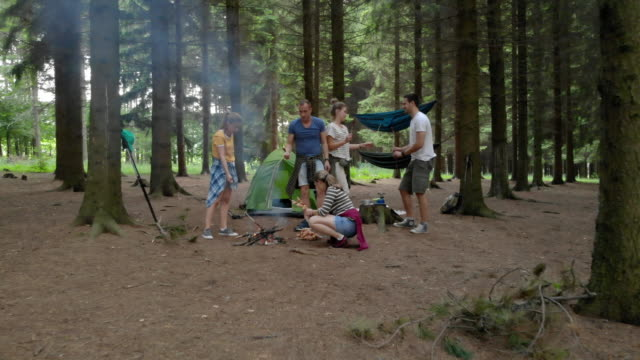 campers preapring food on stick for campfire - campeggio video stock e b–roll