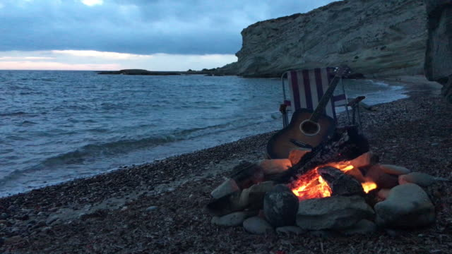 campfire on the beach with guitar - falò spiaggia video stock e b–roll
