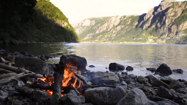 vídeos de stock e filmes b-roll de campfire on the shore of a fjord in norway during summer vacation - fiorde
