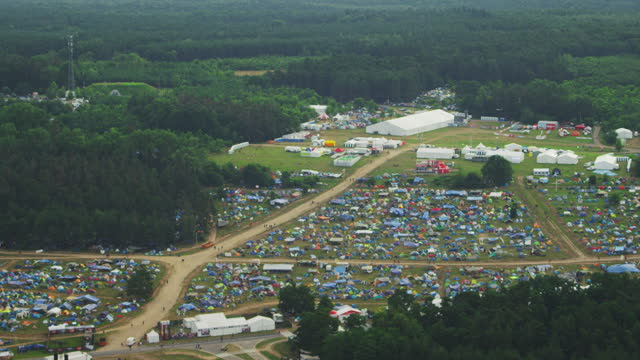 Camping ground at a music festival. Green field and forest. Aerial view