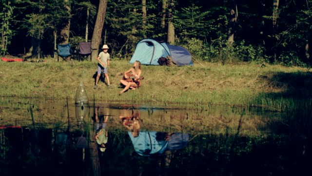 Camping. Woman and her son relaxing with guitar video