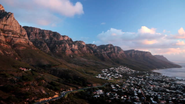 Camps Bay view A wide angle pan of Table Mountain and the Twelve Apostle mountain range above Camps Bay, taken from the slopes of Lion's Head, and filmed just before sunset. table mountain national park stock videos & royalty-free footage
