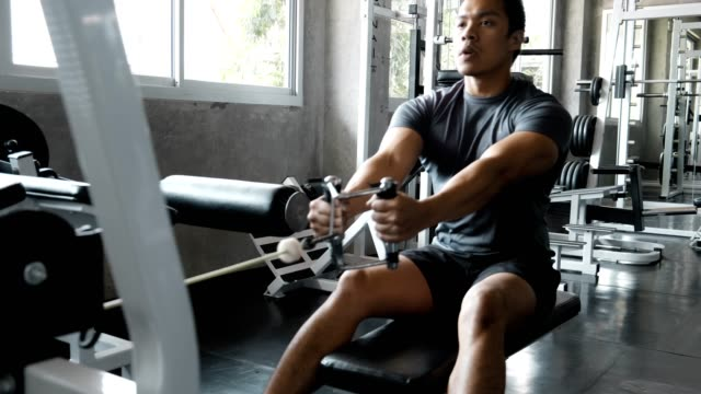 vídeos de stock e filmes b-roll de i can work this low row machine. - aparelho de musculação
