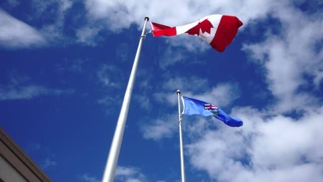 Canada National Flag and Alberta Provincial Flag flying the wind shot from below