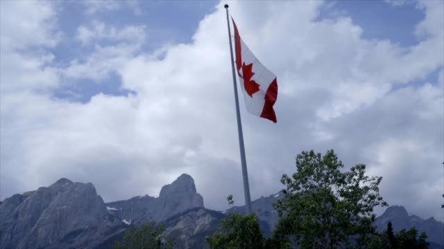 canadian flag against mountain landscape - slow motion - canada flag stock videos & royalty-free footage