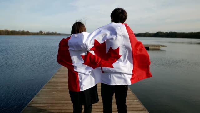 canadian flag in the open air and family emotions - canada day stock videos & royalty-free footage