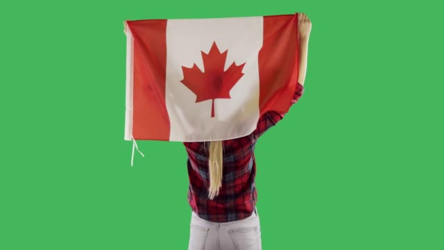 Canadian flag on the back of a woman on chroma key green screen.