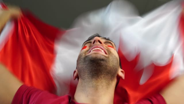 canadian guy celebrating with canada flag - canada day stock videos & royalty-free footage