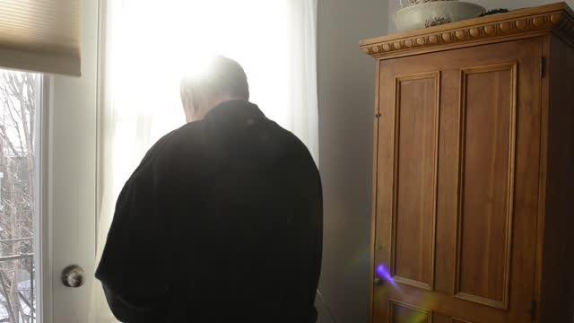 vidéos et rushes de homme canadien utilisant une robe regardant par la fenêtre un matin d'hiver à montréal - peignoir