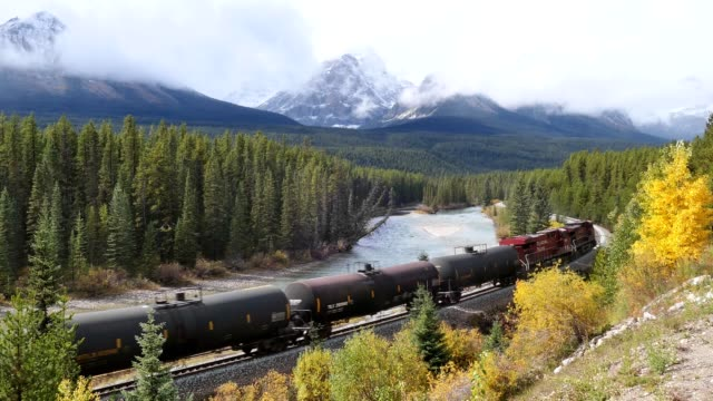 Video Canadian Pacific Railway long freight passing in autumn valley on Bow river at Morant's Curve