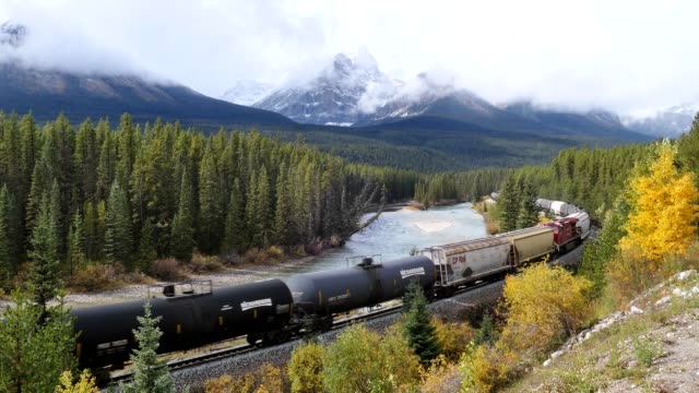 Canadian Pacific Railway long freight passing in autumn valley on Bow river at Morant's Curve