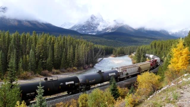 canadian pacific railway lungo trasporto merci che passa nella valle autunnale sul fiume bow alla curva di morant - ferrovia video stock e b–roll