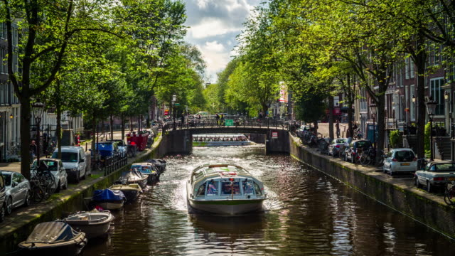 canal in amsterdam with tourboat - canale video stock e b–roll