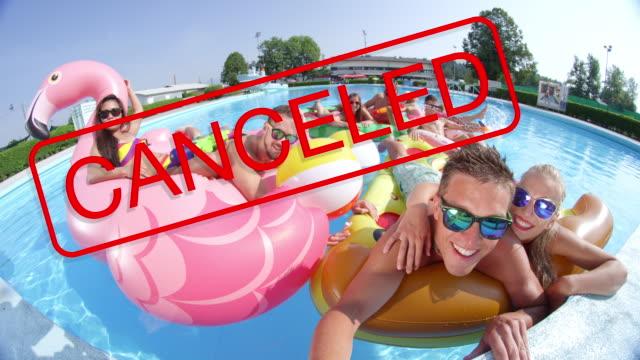 close up: abgesagtes schild bedeckt die lächelnden gesichter von touristen, die am pool feiern - spring break stock-videos und b-roll-filmmaterial