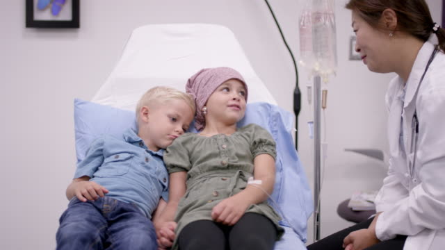 Cancer patient in oncology unit Beautiful little girl with cancer in the oncology unit getting chemotherapy treatment. She is playing with her brother affectionately. mental wellbeing stock videos & royalty-free footage