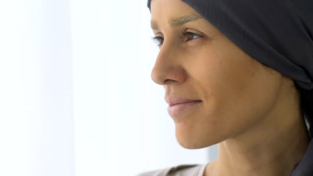 cancer patient smiling and looking out window, resigned to disease, courage - emozione positiva video stock e b–roll