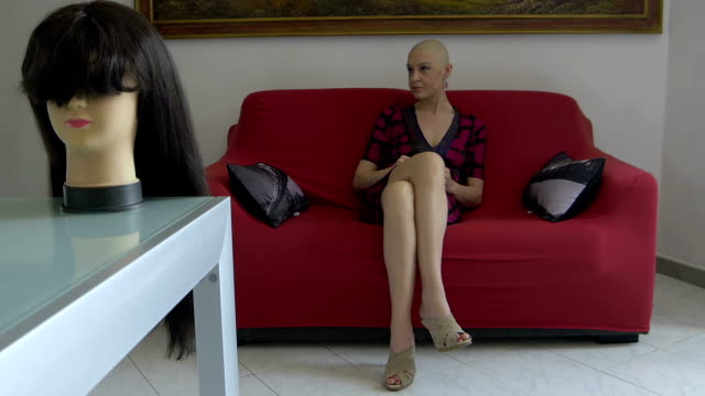 cancer survivor sitting on the couch: wig, loneliness, courage, faith, disease video
