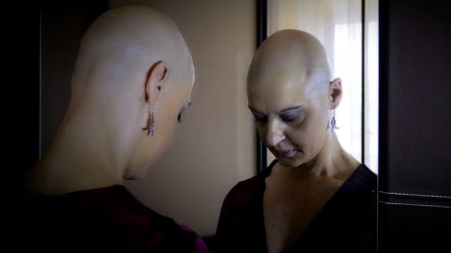 cancer-stricken woman looks in the mirror: loneliness, sadness,  discomfort - meme hayvan vücudu bölümleri stok videoları ve detay görüntü çekimi