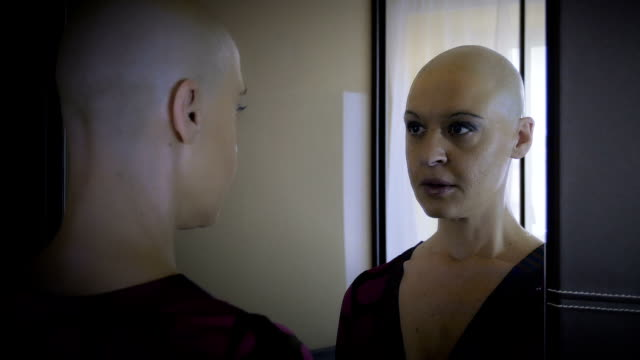 cancer-stricken woman looks in the mirror: loneliness, sadness,  discomfort Real bald cancer survivor woman looking sad into the mirror cancer patient stock videos & royalty-free footage