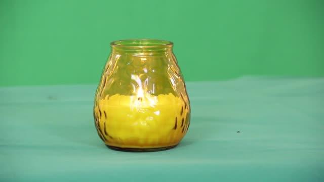 candela in bicchiere giallo su green screen - data scritta video stock e b–roll