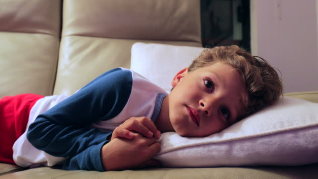 Candid 4K clip of young boy starring at TV screen at night. Child layed in sofa watching screen Candid 4K clip of young boy starring at TV screen at night. Child layed in sofa watching screen boredom stock videos & royalty-free footage