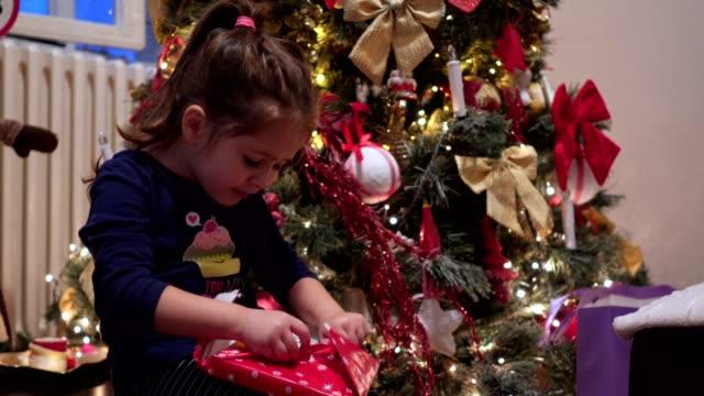 uppriktig känsla av liten flicka uppackning julklapp - christmas gift family bildbanksvideor och videomaterial från bakom kulisserna