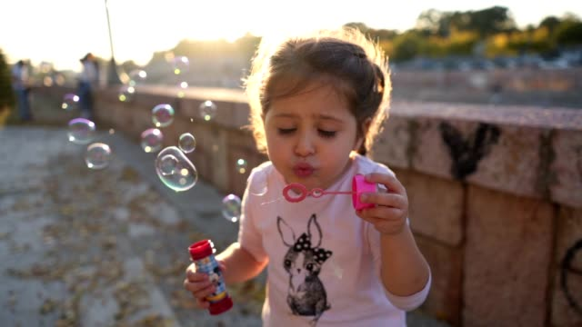 Candid girl playing with a bubble wand