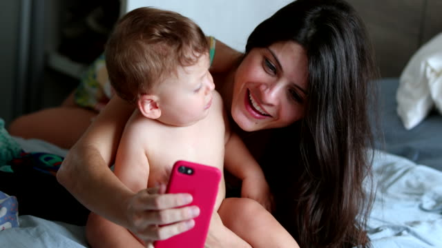 vídeos de stock, filmes e b-roll de mãe sincera tirando selfie com bebê bebê no quarto em casa - mobile