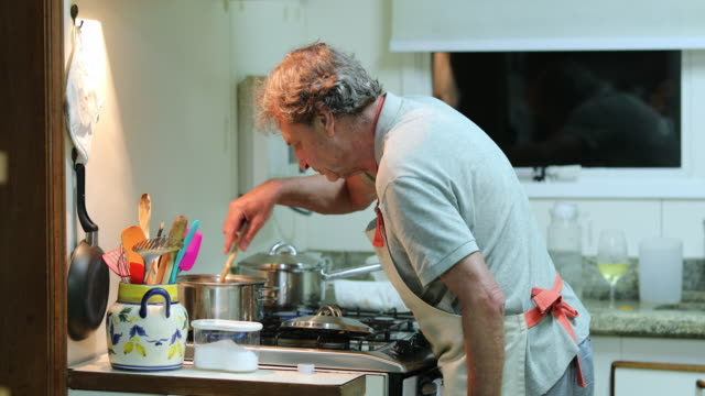 Candid older man cooking at the kitchen in the evening Candid older man cooking at the kitchen in the evening husband stock videos & royalty-free footage