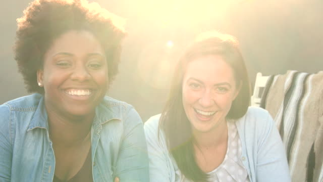 vídeos de stock e filmes b-roll de candid portrait of two women laughing together, lens flare - amizade feminina