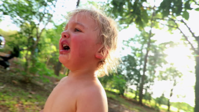 vídeos de stock e filmes b-roll de candid real crying baby outdoors in 4k resolution. casual natural crying infant toddler baby boy outside in the sunlight - criança perdida