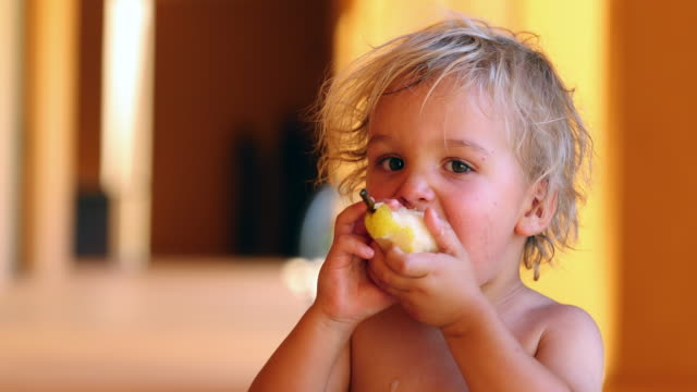 Candid shot of baby boy eating pear fruit outside in the sunlight. 4k clip resolution of baby blonde boy eating healthy fruit