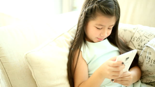 Candid shot of young girl using smartphone on sofa Full HD. video