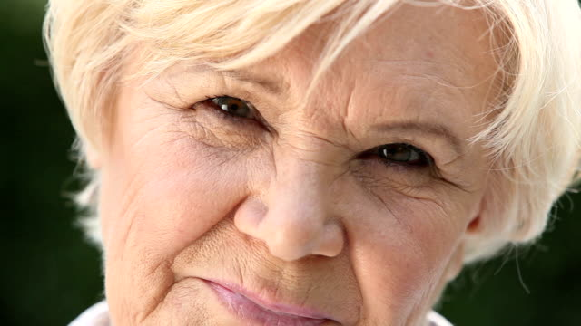 Candid smile Macro shot of a retired woman with a candid smile sideways glance stock videos & royalty-free footage