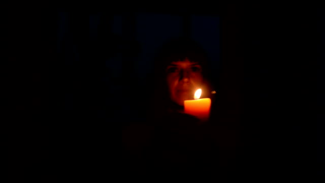 Candle. A girl lights a candle in a dark room video