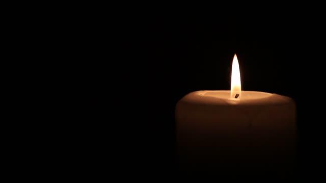 Candle burning on black background