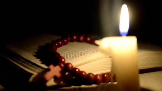 Ardor de vela en el fondo de la Sagrada libro y una cruz - vídeo