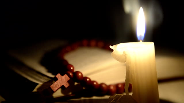 Candle burning on the background of the holy book and a cross