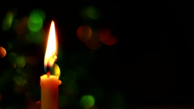 Candle lit in front of festive lights Christmas tree video