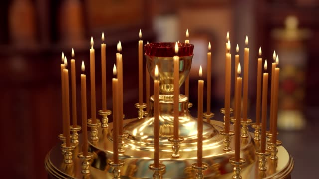 candle on candlestick holder in church - candeliere video stock e b–roll