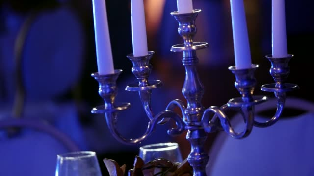 candleholder with candles burns in dark restaurant, wax candles in candlesticks, decorative candles burning, decoration of the banquet hall, shallow depth of field - candeliere video stock e b–roll