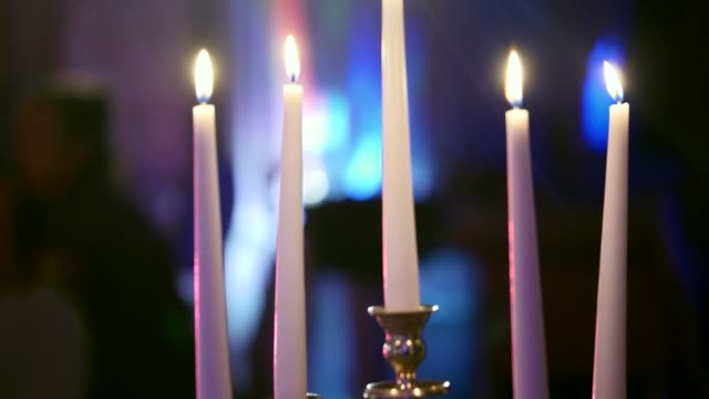 Candleholder with candles burns in dark restaurant, wax candles in candlesticks, decorative candles burning, decoration of the banquet hall, shallow depth of field video