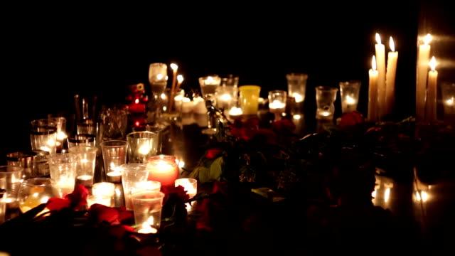 kerzen und blumen am denkmal in erinnerung an die opfer der opfer des terroranschlags. menschen trauern und suchen sie nach verwandten und freunden. trauer und verzweiflung. militärische aktionen, politik, terrorismus - mahnwachen stock-videos und b-roll-filmmaterial