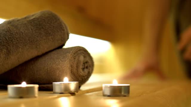 candles and towels close up shot in sauna - zabieg spa filmów i materiałów b-roll