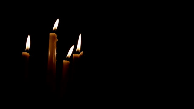 candles blowing on solid black background - candeliere video stock e b–roll